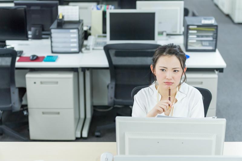 パソコンを前に考える女性
