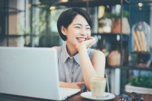 パソコン前で笑顔の若い女性
