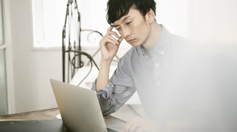 PCの画面を見て悩む男性