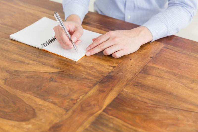 ノートにメモをしている男性