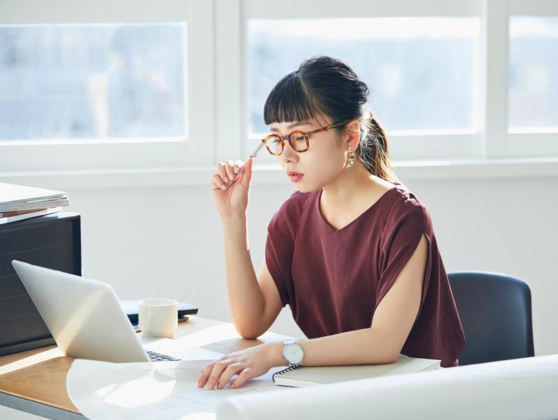 パソコンを見て考える様子の女性