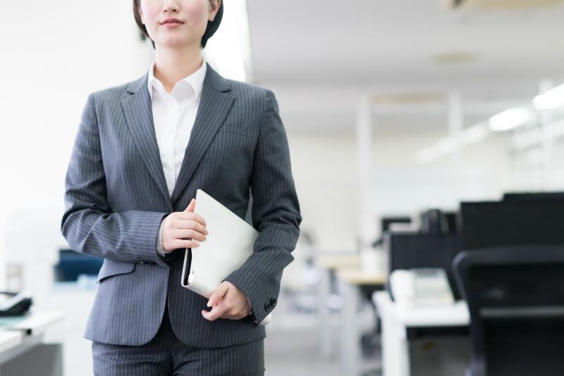 バインダーを抱えてオフィス内を歩いている女性