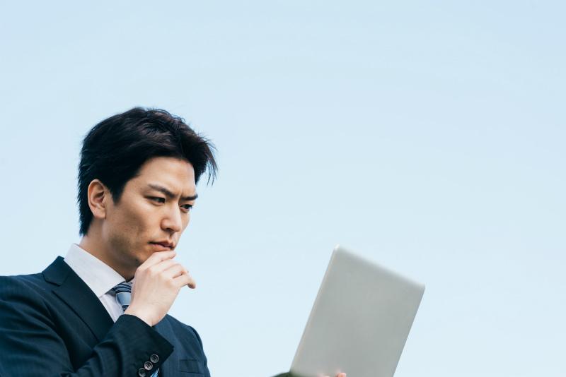 屋外でノートPCを開いている若い男性