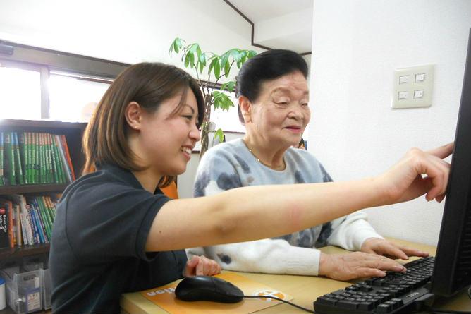 生徒にパソコンを教えるディードットステーションのスタッフ